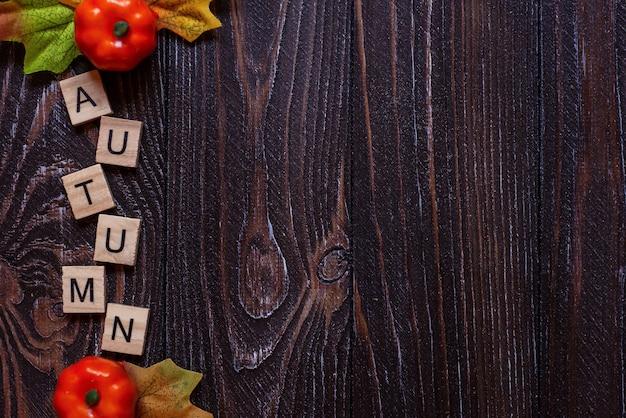 文字の碑文は、木製の背景に立っていますぼやけたカラフルな秋の秋の言葉