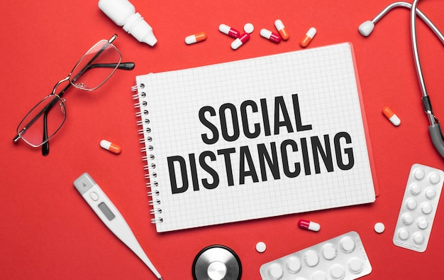 Надпись социальное расстояние на записной книжке на медицинскую тему. рабочее место врача.