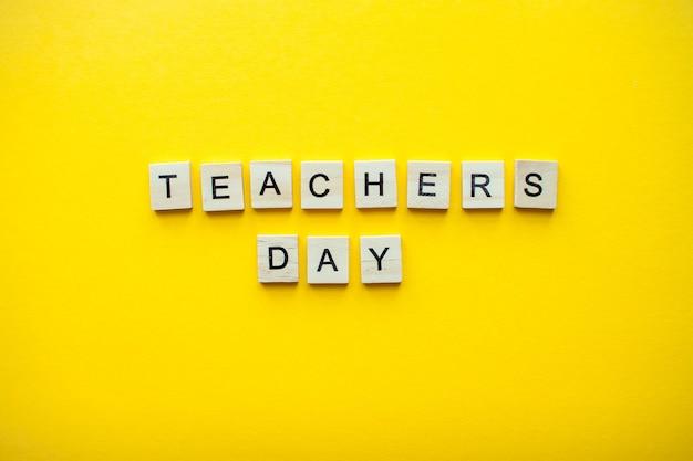밝은 노란색 배경에 나무 블록에서 비문 교사의 날