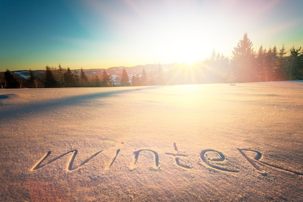晴れた凍るような冬の日の森と丘を背景に雪の上の碑文の冬。冬時間と冬のアウトドアレクリエーションの概念