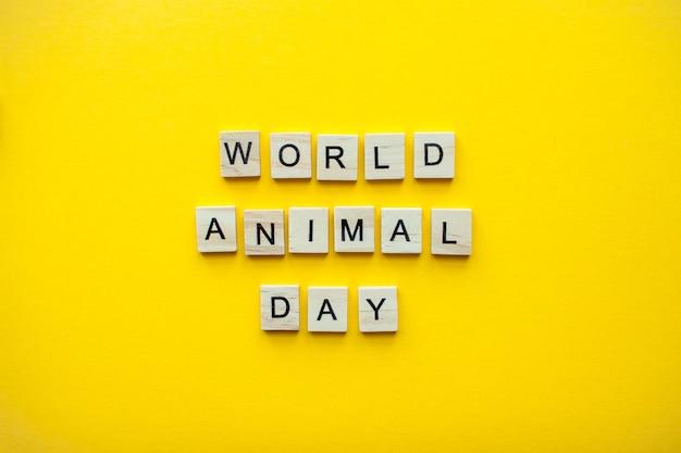밝은 노란색 배경에 나무 블록에서 비문 세계 동물의 날