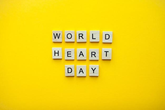밝은 노란색 배경에 나무 블록에서 비문 세계 심장의 날
