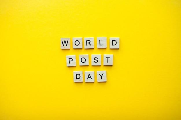 밝은 노란색 배경에 나무 블록에서 비문 세계 포스트 날