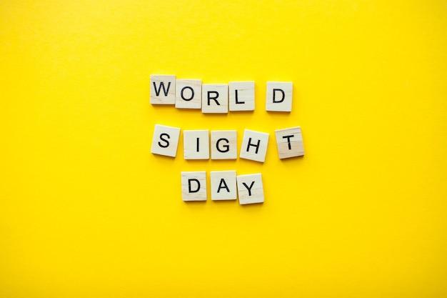 밝은 노란색 배경에 나무 블록에서 비문 세계 시력의 날