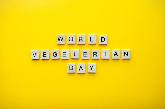 밝은 노란색 배경에 나무 블록에서 비문 세계 채식주의의 날