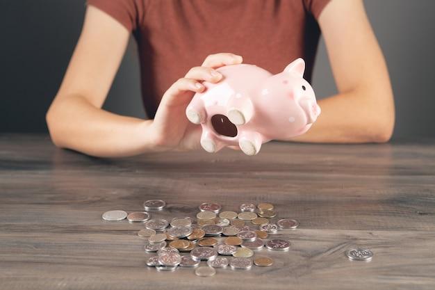 테이블에 돼지 저금통의 내부입니다. 돼지 저금통을 들고 앉아있는 여자