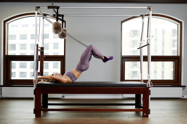 강사는 리포머에서 운동을 하고, 아름다운 소녀는 현대 리포머 시뮬레이터에서 깊은 근육을 단련하기 위해 훈련하고, 현대화된 필라테스 및 요가용 리포머 장비를 사용합니다.