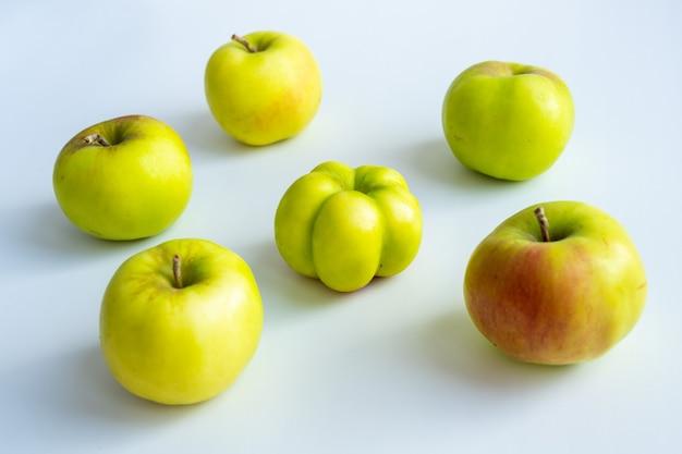 흥미롭고 특이하고 이상한 사과. 평범한 사과에 둘러싸인 못생긴 사과. 사진은 개성, 리더십, 개인 특성, 자기 수용을 상징합니다.