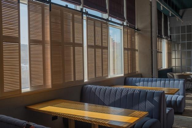 아늑한 카페의 내부는 화창한 날과 바닥에 아름다운 그림자가 있습니다.