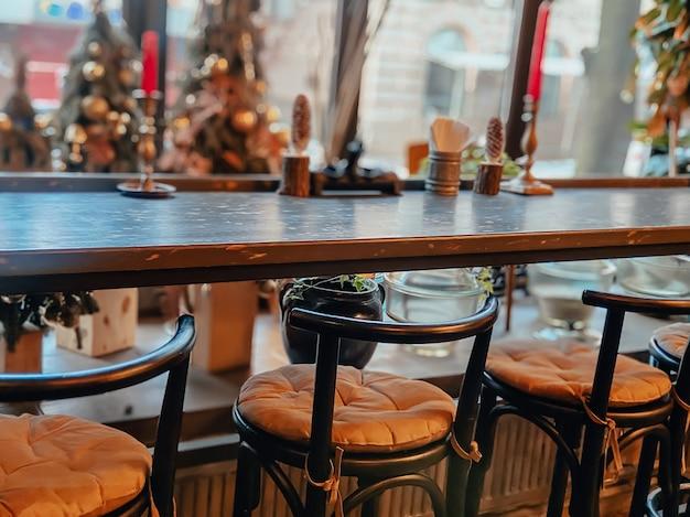 Интерьер уютного ресторана со столиками у окна с видом на город.