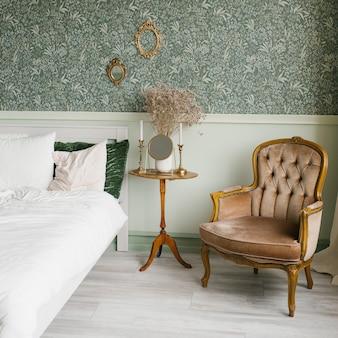 Интерьер спальни в неоклассическом стиле. кровать с подушками и классическое кресло возле тумбочки, на которой в вазе засохшие цветы.