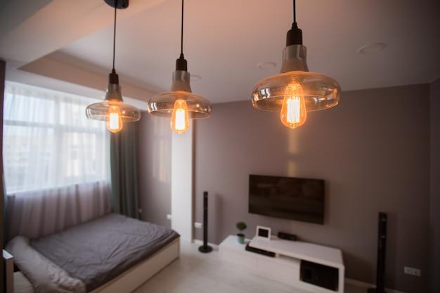 小さなアパートのインテリア。エジソンの白熱電球を通して見る