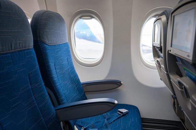 航空機のインテリア。空の飛行機のキャビン。ヘッドレストにスクリーンを備えた助手席の列