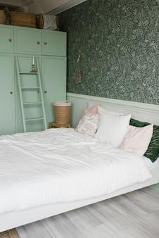 ベッドルームのインテリアはモダンなスタイルです。ミントのワードローブとカラフルな枕付きの白いベッド