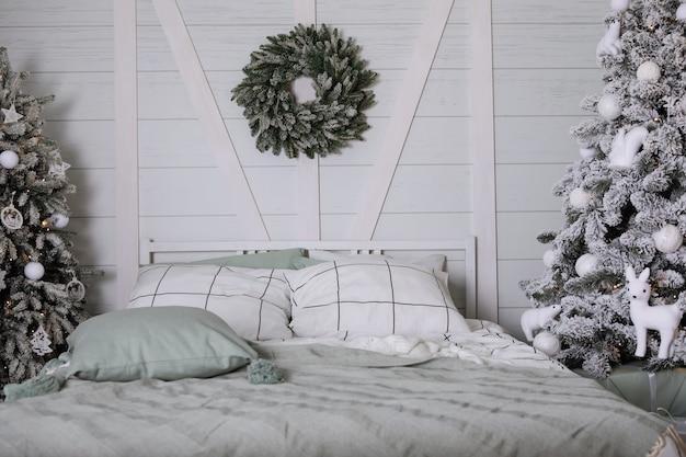 베개가 있는 침대, 크리스마스 트리, 회색 색조의 헤드보드에 화환이 있는 침실 내부.