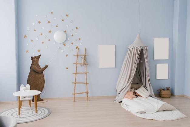 어린이 방의 내부는 파란색과 베이지 색으로 꾸며져 있습니다. 곰은 손에 작은 풍선을 들고 있습니다. 플라스틱 공으로 만든 수영장으로 슬라이드하십시오. 베개와 장난감이 있는 텐트 침대