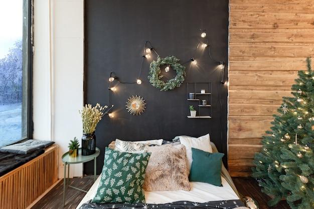 시골집의 내부는 새해 나무로 장식되어 있습니다. 심플한 목재 가구와 목재로 장식 된 넓고 밝은 방