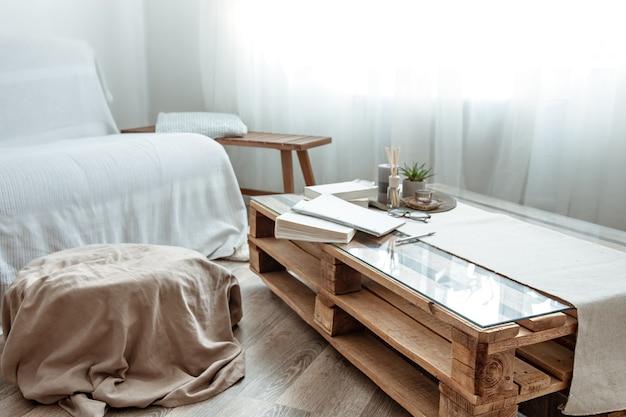 部屋のインテリアはスカンジナビアスタイルで、窓際に本が置かれた小さなテーブルがあります。