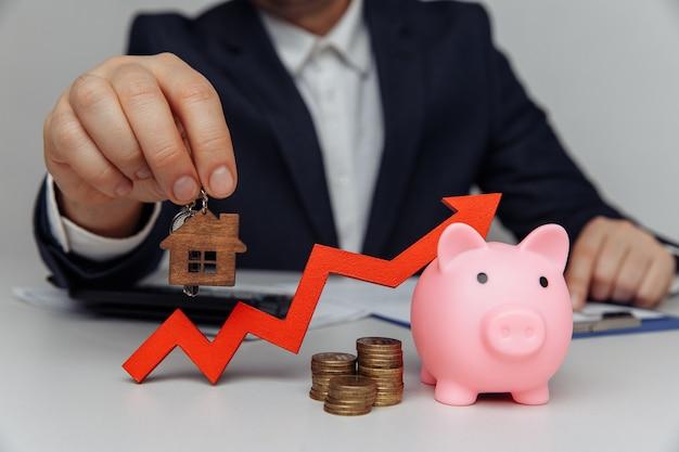 투자자의 손을 잡고 집 열쇠. 사업 투자 아이디어. 부동산 투자의 개념.