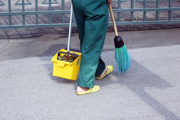 管理人は落ち葉から街の歩道を一掃しました