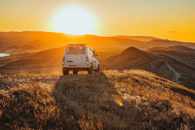 夕焼けの山の頂上にジープが立っている楽しい風景