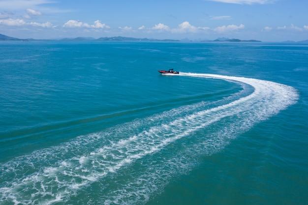 제트 스키는 푸른 물을 통해 빠른 속도로 이동하여 거품 흔적을 남깁니다.