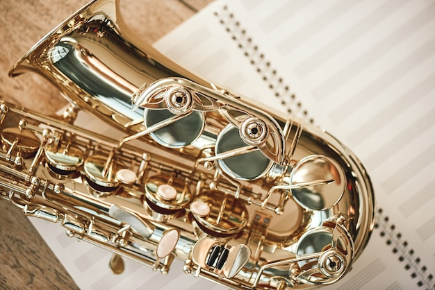 Удовольствие от саксофона. вид сверху на красивый блестящий саксофон, лежащий на листах для нот над деревянным полом. музыкальные инструменты. музыкальное оборудование.