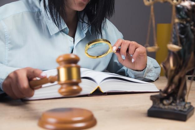 裁判官は正義の像の前に座っているハンマーで殴る