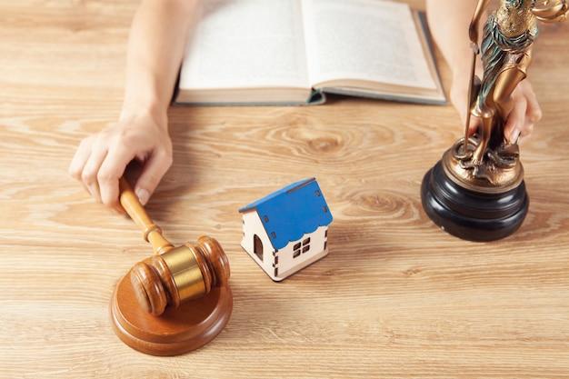 裁判官のハンマーとテーブルの上の家