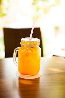 木製のテーブルにカクテルストローと新鮮なオレンジジュースでいっぱいのjurカップ