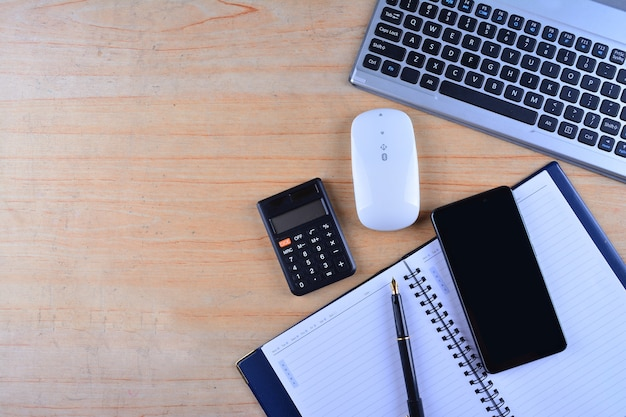 Клавиатура с мышью, перьевая ручка, блокнот, калькулятор и смартфон на столе