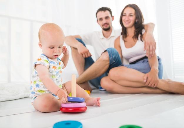 Малыш собирает пирамиду на фоне родителей