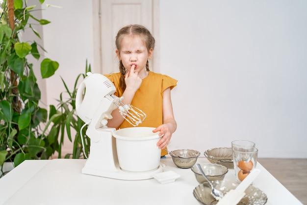 Малышка готовит тесто или крем в погружной миксере