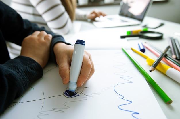 Ребенок рисует, пока его мама работает с ноутбуком