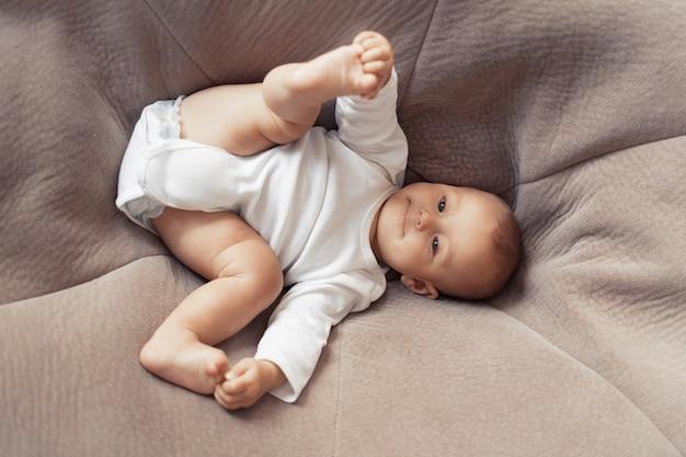 아이가 누워서 거대한 베개에 놀아요