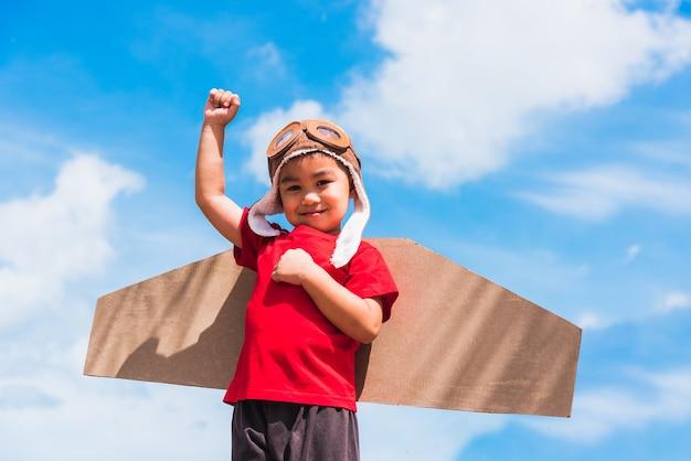 Ребенок маленький мальчик улыбается в шляпе пилота и в очках играет в игрушечный самолетик из картона