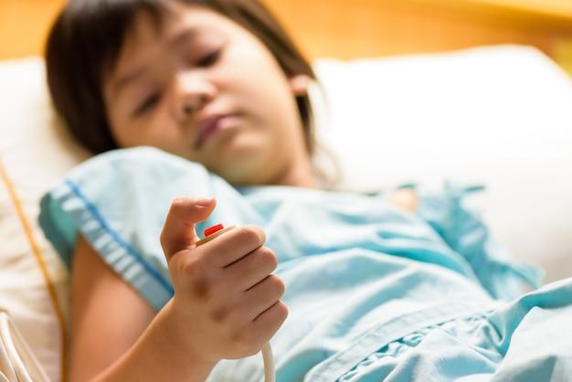 子供の患者は緊急電話ボタンを手にしている。