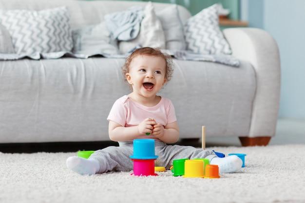 子供は明るいおもちゃが付いている軽いカーペットの床で遊んで、塔を建てます