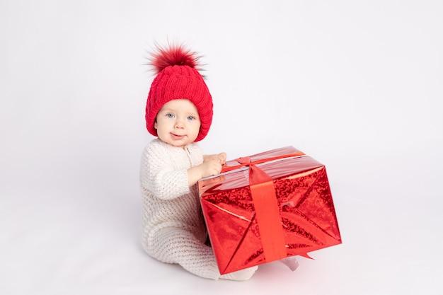 흰색 격리된 배경에 빨간 모자와 선물을 가진 아이, 텍스트를 위한 공간, 새해와 크리스마스의 개념