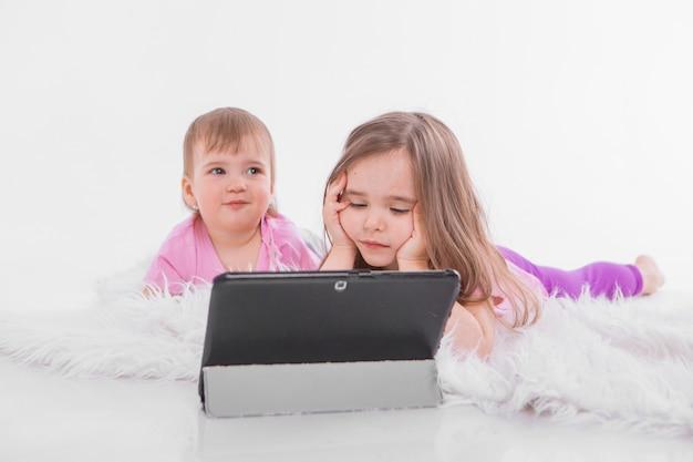 Дети смотрят мультики на планшете