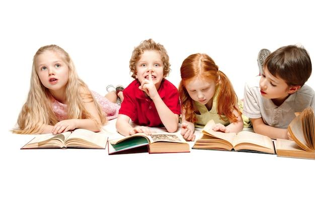 スタジオで本を持って横たわっている子供たちの男の子と女の子、笑顔、笑い、白で隔離。本の日、教育、学校、子供、知識、子供時代、友情、研究と子供の概念