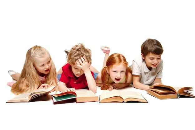 Дети мальчик и девочки кладут книги в студии, улыбаясь, смеясь, изолированные на белом. день книги, образования, школы, ребенка, знаний, детства, дружбы, учебы и концепции детей