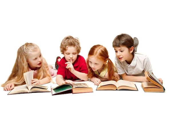 아이 소년과 소녀 스튜디오에서 책과 함께 누워 웃 고, 웃 고, 흰색 절연. 책, 교육, 학교, 아이, 지식, 어린 시절, 우정, 연구 및 어린이 개념의 날