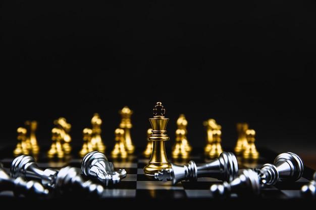 落下する銀のチェスの真ん中に立っている黄金の王チェス。
