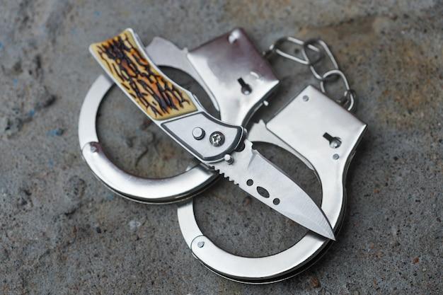 На нож надеты наручники. понятие преступления. фото высокого качества