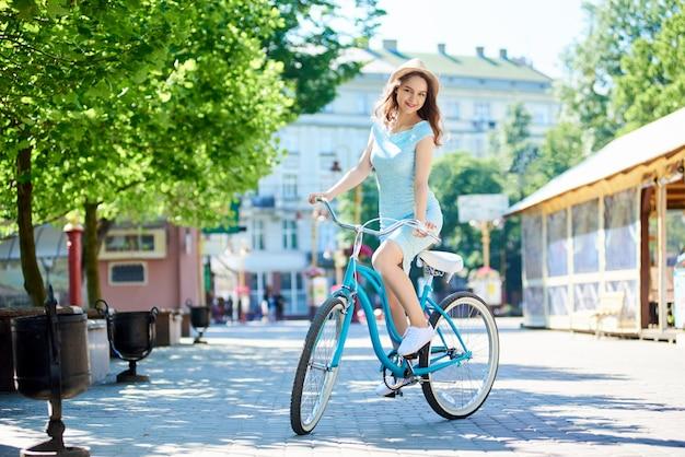 복고풍 자전거를 탄 여인은 여름 도시의 거리에서 카메라를 신비롭게 본다.