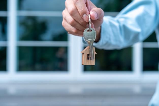 Арендодатель или торговый представитель передает ключ новому домовладельцу.