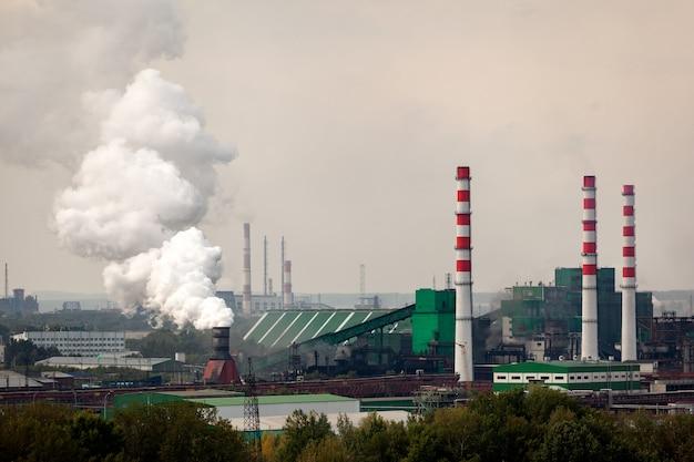 거대한 연기 퍼프가 나오는 공장과 높은 크레인이있는 거대한 산업 도시의 풍경. 식물과 산업에 의한 환경 오염