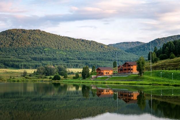 Пейзаж гор и озер с объективным небом. роскошный дорогой особняк из дерева в экологически чистом горном районе отражается в воде у озера.