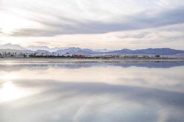 Пейзажное небо отражается в море. береговая линия города с горами на горизонте.